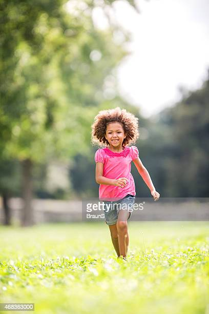 Little African American girl having fun while running outdoors.