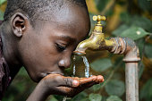Symbol for Hope and Malnutrition in Africa. Little African boy happy finally getting water.