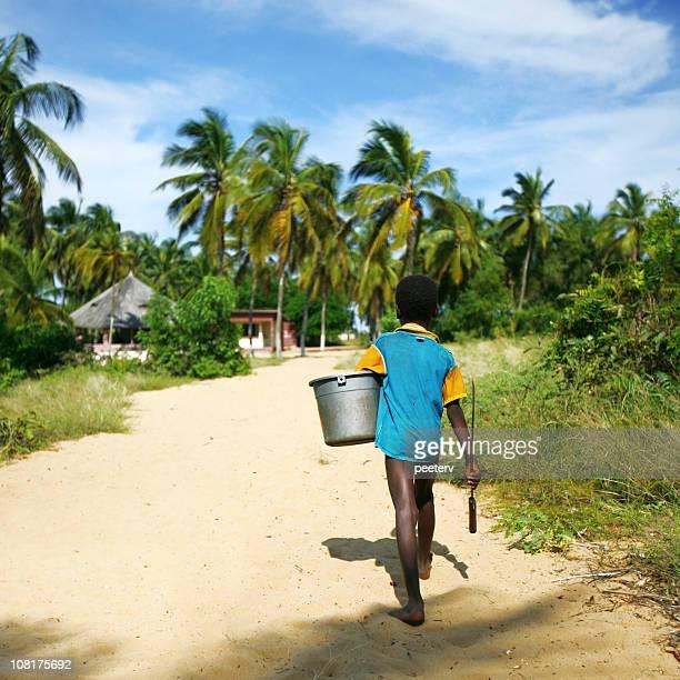 Piccolo ragazzo africano cammina lungo la strada