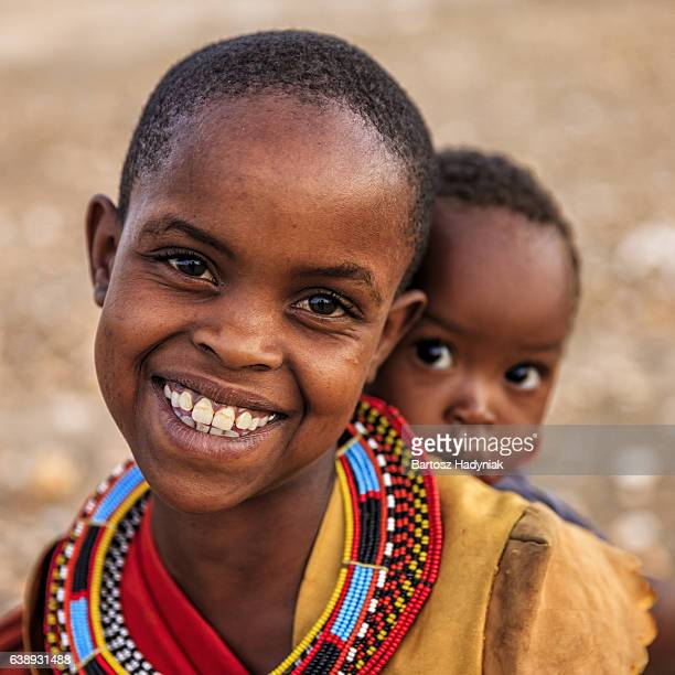 Little African girl carrying her baby brother, Kenya, East Africa