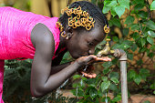 Beautiful little African girl drinking outdoors some healthy water from a tap in Bamako, Mali. Symbol for life and health in African countries.