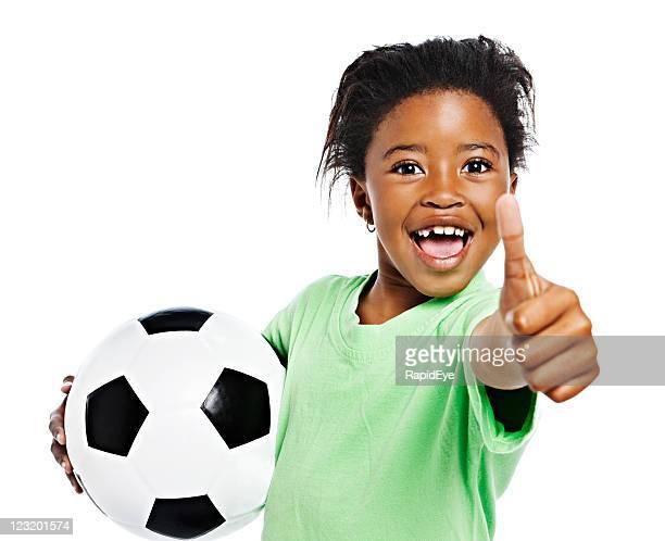Kleine Afrikanische Mädchen mit Fußball ball für erfolgreiche Daumen hoch.