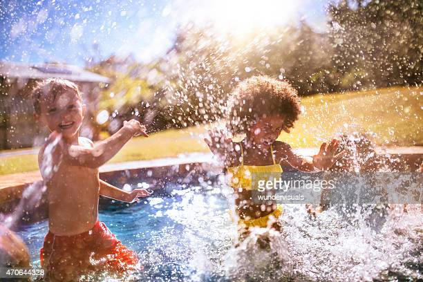 Little Afro girl and friend splashing water in swimming pool
