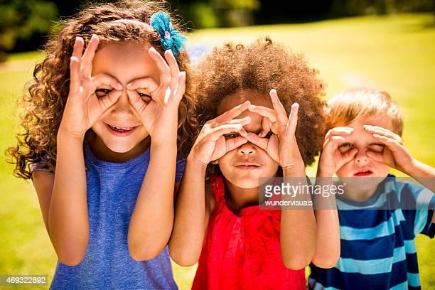 Petite fille Afro et amis faire des lunettes avec ses mains