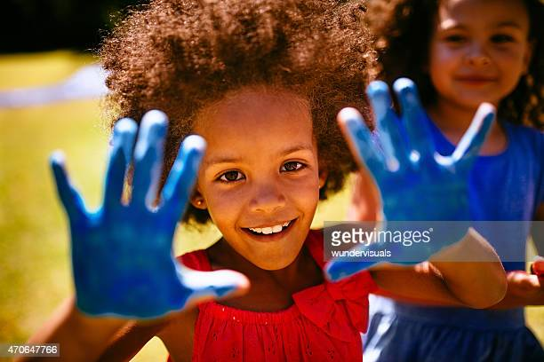 Little Afro girl showing hands full of blue paint