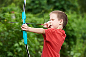 Little archer with bow and arrow outdoors