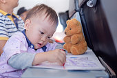 Little Asian 1 year old toddler boy coloring in coloring book with crayons during flight on airplane. Flying with children, Flight entertainment for kids, Happy air travel & little traveler concept