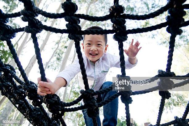 Petit garçon asiatique, grimper de corde