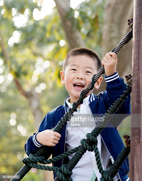 Piccolo ragazzo asiatico in piedi su corda bridg