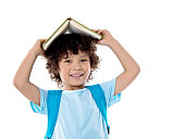 Little asian boy with a book against white background.