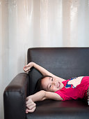 little asian child girl kid stretch oneself  on the sofa after her daytime sleepiness