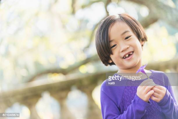 Little Asian girl holding purple flower