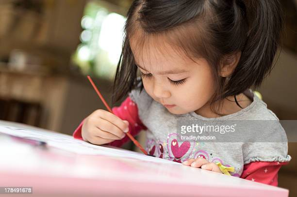 Little Asian girl learning to paint with watercolors at home