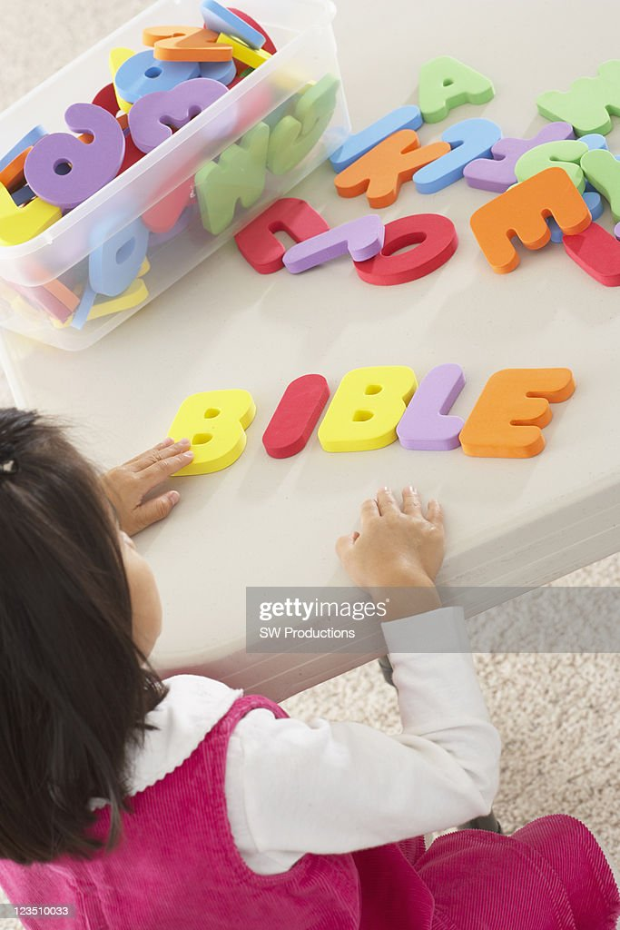 Little Asian girl playing with sponge play letters spelling 'Bible' : Stock Photo