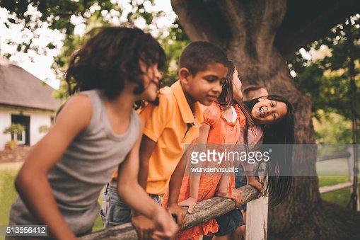 小さなアジアの女の子笑顔をフェンスでご友人とご一緒に公園