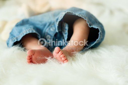 little baby boy feet baby lie down in bed in the afternoon stock