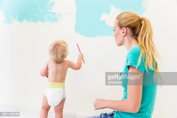 Little baby boy in diapers painting the walls of his new room