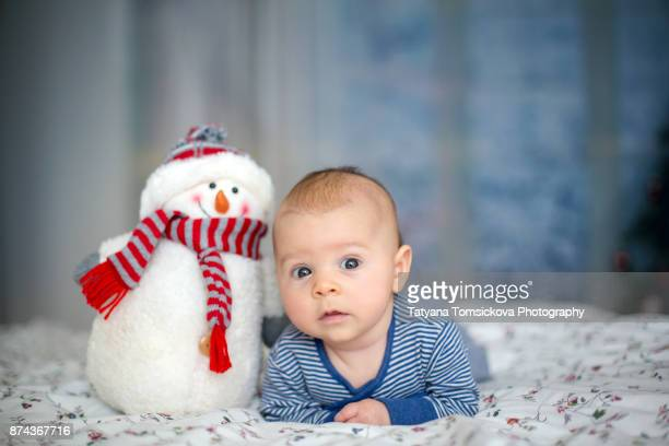 Little baby boy, playing with big snowman at home, wintertime