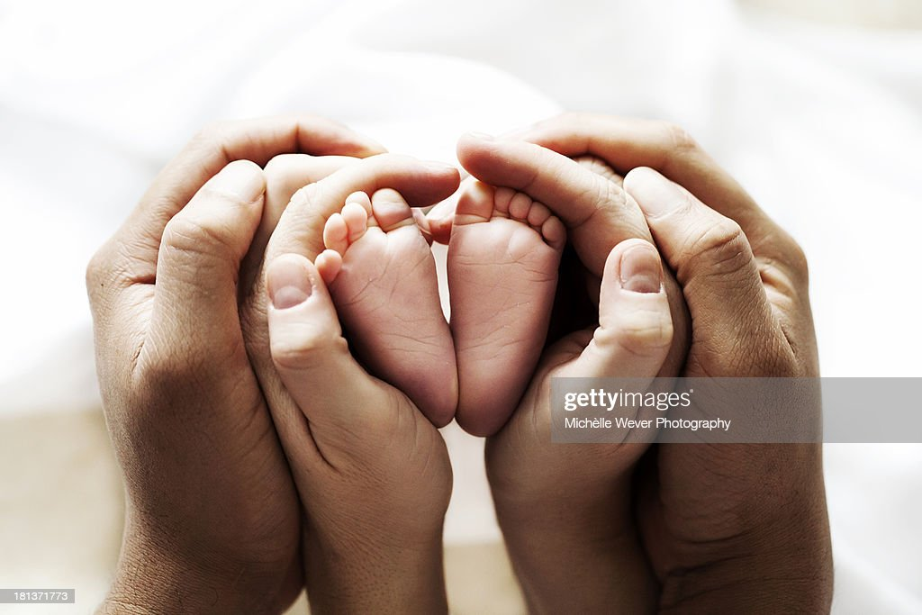 2 hands holding baby feet