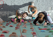 Little baby girl doing first steps on climbing wall while Happy Parents teaching her