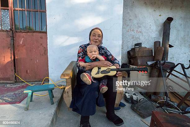 A little baby in his grandmother's hug sitting before a rural house Around 61 million children are left behind in China's rural villages and towns...