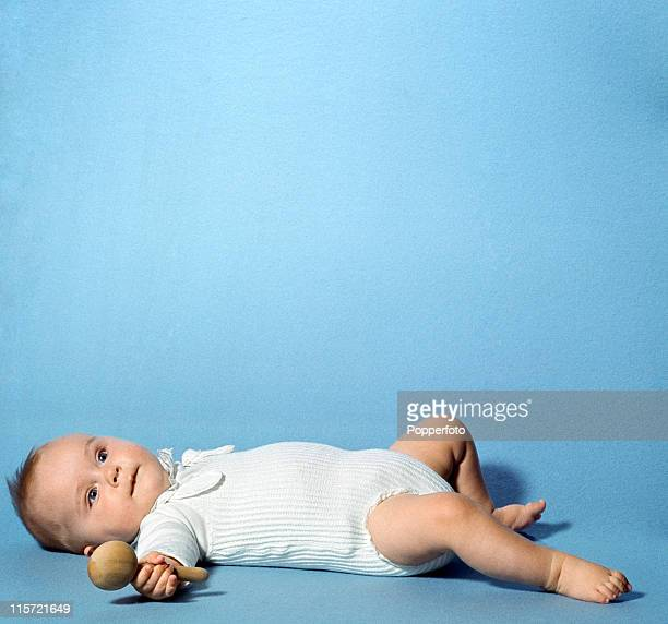 A little baby with a wooden rattle lying on his back wearing a white sleepsuit in a studio setting circa 1967