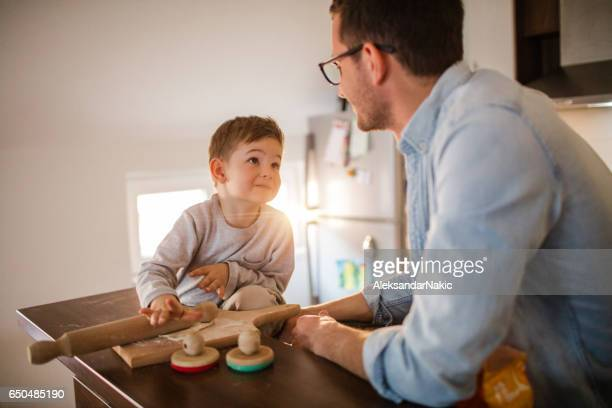 Little baker and his father making a bread