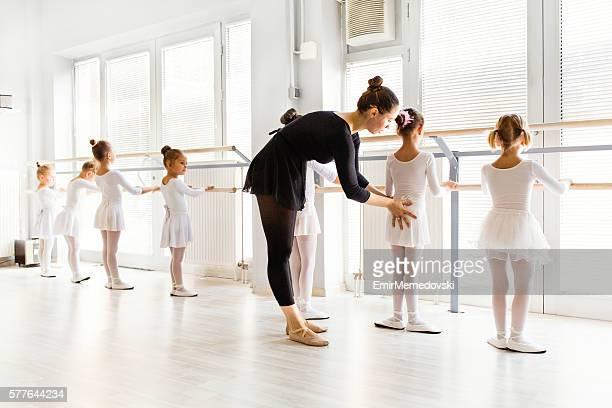 Little ballerinas with personal ballet teacher in dance studio.