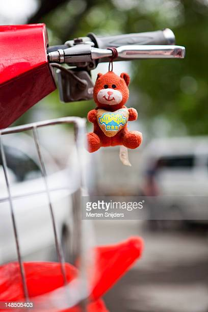 Little bear hanging from handle bar of moped.