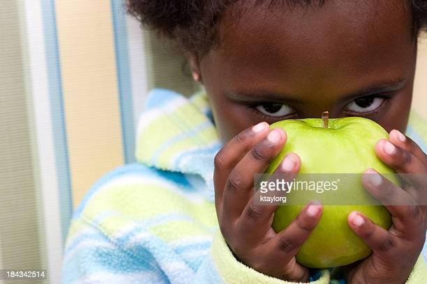 Little beauty peeks from behind apple