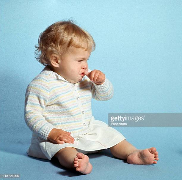 A little blond baby sitting sucking her thumb and about to cry wearing a white skirt and white striped cardigan in a studio setting circa 1967
