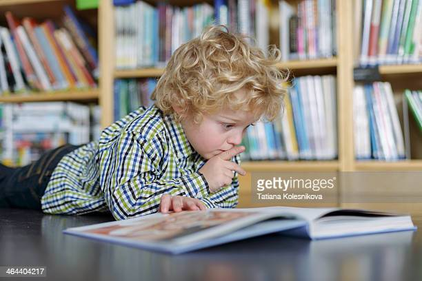 Little blond boy reading a book in a library