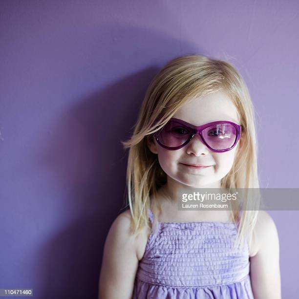 Little blond girl all in purple with sunglasses
