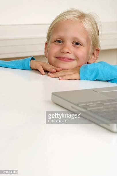 Little blond girl peering over the edge of a table, close-up