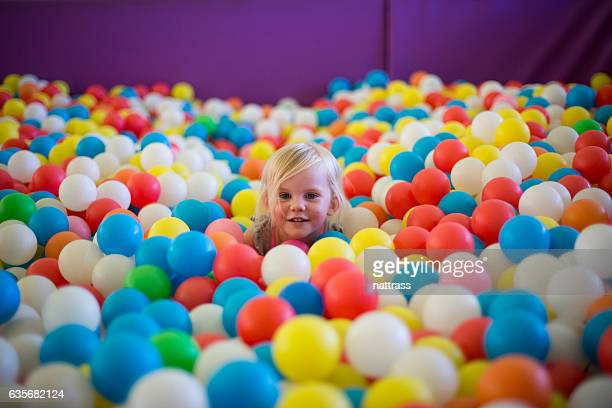 Little blond girl plays in a colorful ball pool