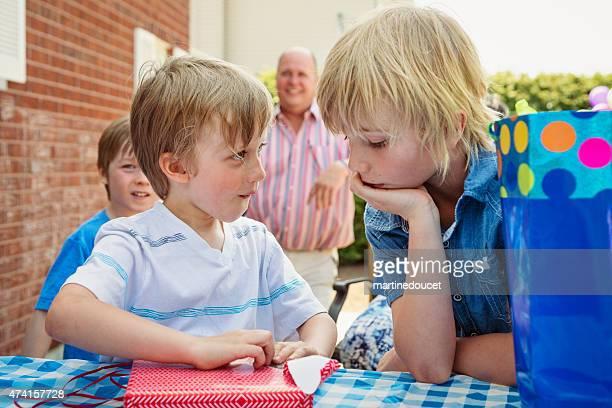 Petit garçon sur le point d'ouvrir son anniversaire présente à l'extérieur.
