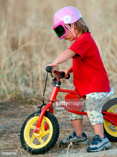 Little Boy Age 3 Years Learning To Ride Bicycle, Wearing Pink Helmet In Garden