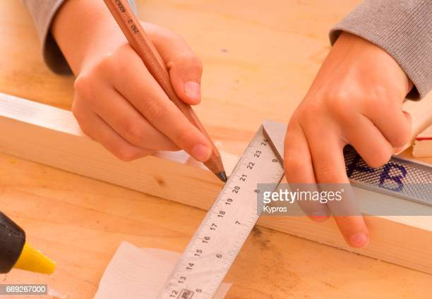 Little Boy Age 7 Years Measuring Wood To Be Cut For Toy Making