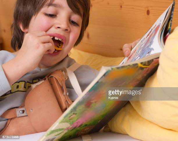 Little Boy Age 7 Years Reading A Comic Book