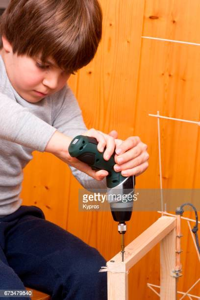 Little Boy Age 7 Years Using An Electric Power Screwdriver To Build Wooden Toy