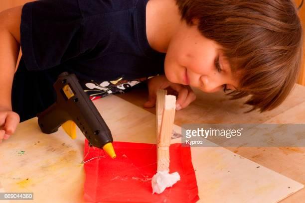 Little Boy Age 7 Years Using Hot Melt Glue Gun