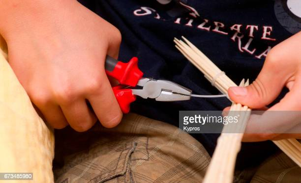 Little Boy Age 7 Years Using Pair Of Pliers To Build Wooden Toy