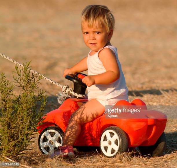 Little Boy Age One Year Driving Red Plastic Toy Car