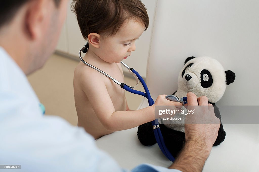 Little boy and doctor using stethoscope on panda toy : Stock Photo