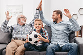 Little boy sitting on couch in living room and holding soccer ball, while his father and grandfather are high-fiving each other