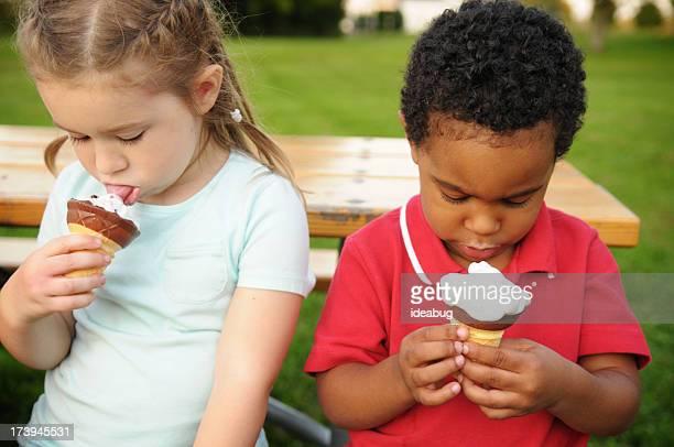 Petit garçon et fille manger cornets de glace à l'extérieur