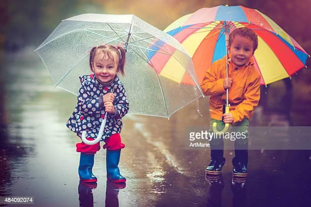 Piccolo ragazzo e ragazza in pioggia