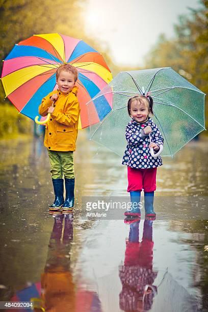 Kleine Jungen und Mädchen im Regen