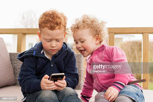 Little boy and girl looking at cell phone