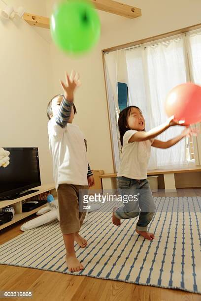 Little boy and girl playing with balloon in room